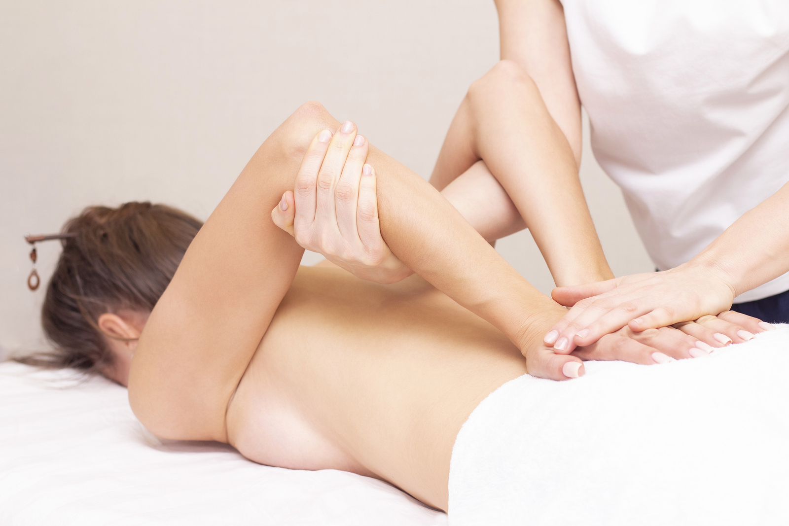 Massage and body care. Spa woman body massage with hands treatment. Stretching the back muscles. Woman having massage at the spa for beautiful girl