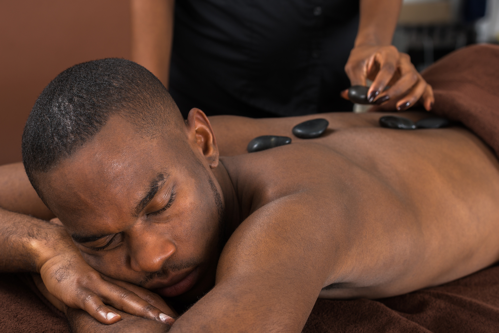 African Man Relaxing In A Spa Getting Hot Stone Therapy